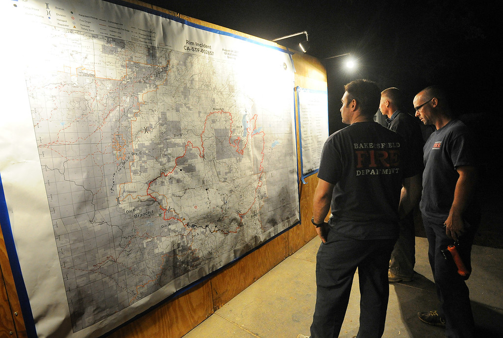 . A trio of Bakersfield firefighters check an updated Rim Fire incident report map that is posted at the incident command post 7 miles east of Groveland, after a long hard day of fighting the fire, which continues to go uncontrolled in the Stanislaus National Forest Saturday Aug. 24, 2013.