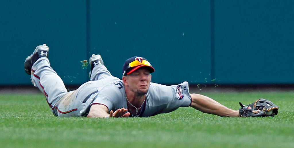 . Twins center fielder Clete Thomas hits the turf after making a diving catch on a fly ball by Detroit\'s Omar Infante in the seventh inning, ending a Tigers rally.   (AP Photo/Duane Burleson)