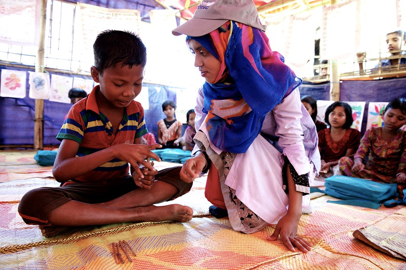 0111-0113Mohammad Sabbir, a 13-year-old disabled Rohingya child, attends classes at a UNICEF-supported learning centre at the Balukhali makeshift settlement for Rohingya refugees in Ukhia, Cox's Bazar, Bangladesh.    Photo: UNICEF / b.a.sujaN/Map