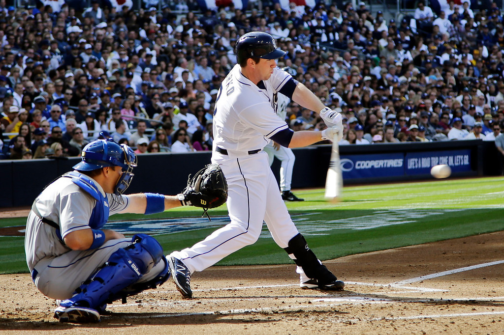 . San Diego Padres\' Jedd Gyorko hits an RBI-single as Los Angeles Dodgers catcher A.J. Ellis watches during the first inning of a baseball game in San Diego, Tuesday, April 9, 2013. (AP Photo/Lenny Ignelzi)