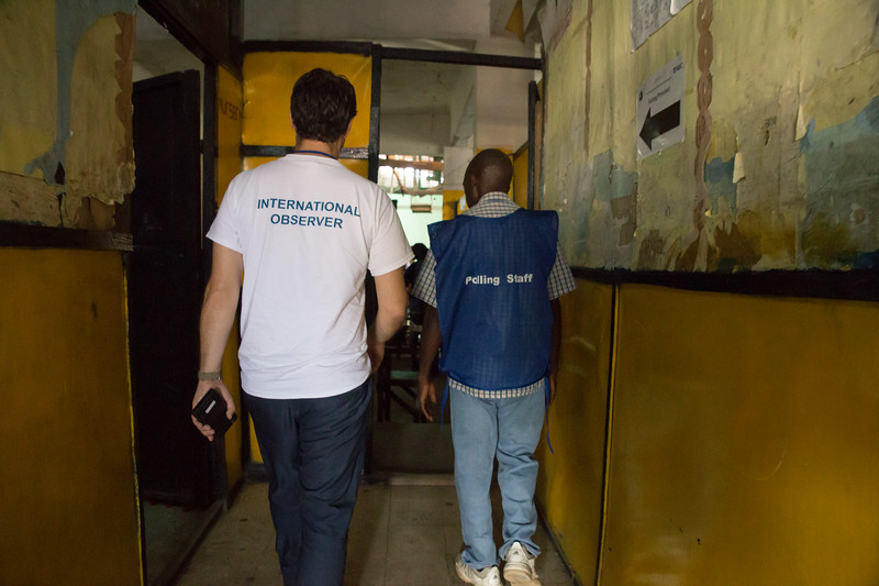 Monrovia, Liberia October 10, 2017 -  Jason Carter walks with a worker at a polling station on election day.