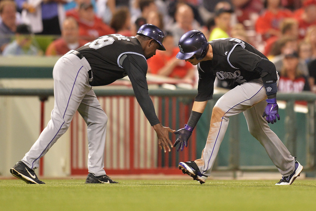 . CINCINNATI, OH - MAY 10: Troy Tulowitzki #2 of the Colorado Rockies is congratulated by third base coach Stu Cole #39 of the Colorado Rockies as rounds third base after his solo home run in the sixth inning against the Cincinnati Reds at Great American Ball Park on May 10, 2014 in Cincinnati, Ohio. Colorado defeated Cincinnati 11-2. (Photo by Jamie Sabau/Getty Images)
