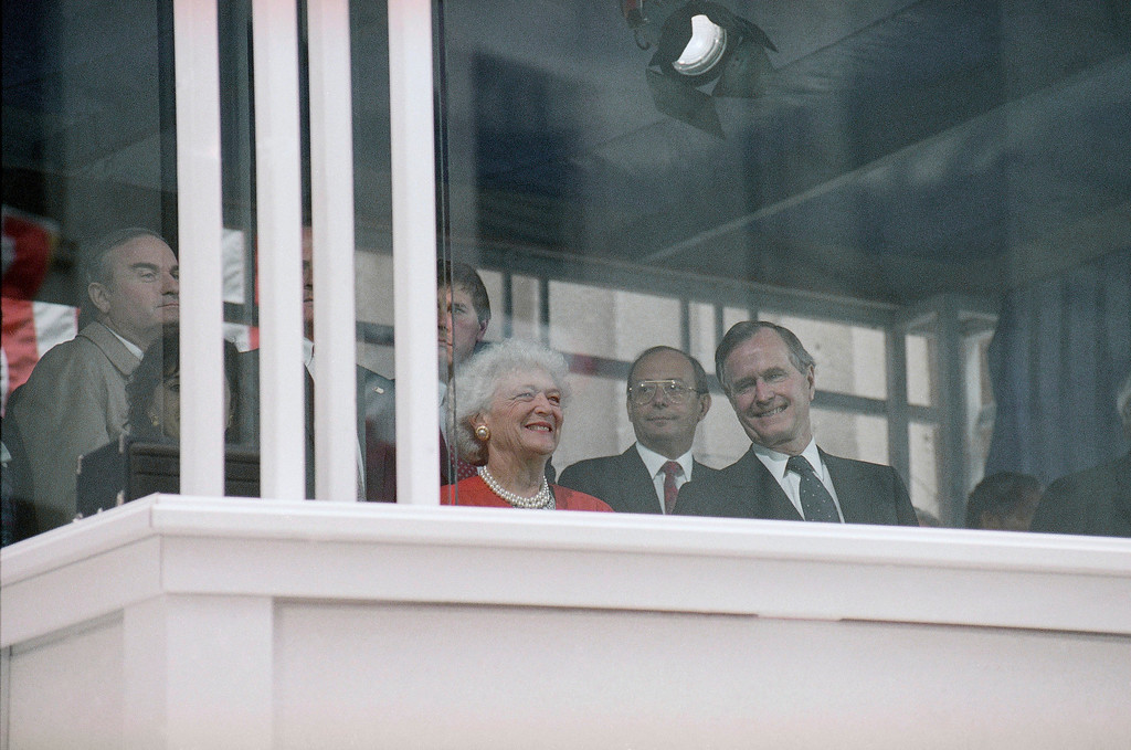 . President George H. W. Bush, right, and First Lady Barbara Bush, left in red, sit behind bullet-resistant barriers as they watch festivities marking the 200th anniversary of President George Washingtons inaugural at the Federal Hall National Memorial, with, New York Sen. Alfonse DAmato, sitting behind the president, Sunday, April 30, 1989, New York. (AP Photo/Richard Drew)