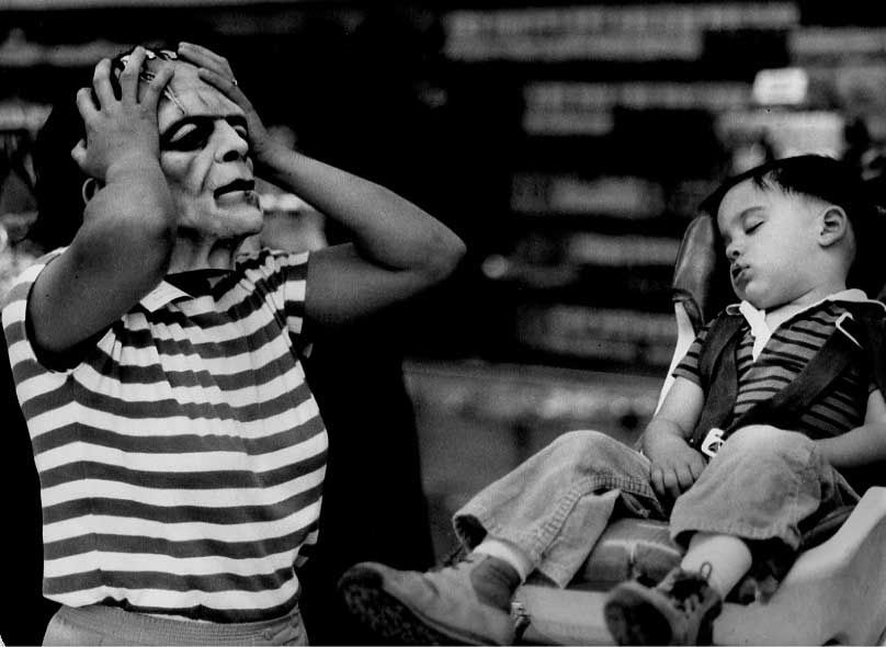 . 1983: Cathy Humphry tries on masks while son Anthony, 2, dozes at Victoria\'s Theatrical Supply. (Michael J. Bryant, Mercury News)