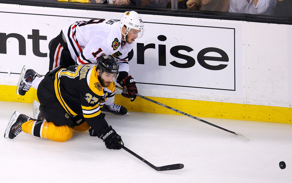 . Boston Bruins\' Patrice Bergeron (37) and Chicago Blackhawks\' Jonathan Toews battle for the puck during the second period in Game 6 of their NHL Stanley Cup Finals hockey series in Boston, Massachusetts, June 24, 2013. REUTERS/Brian Snyder
