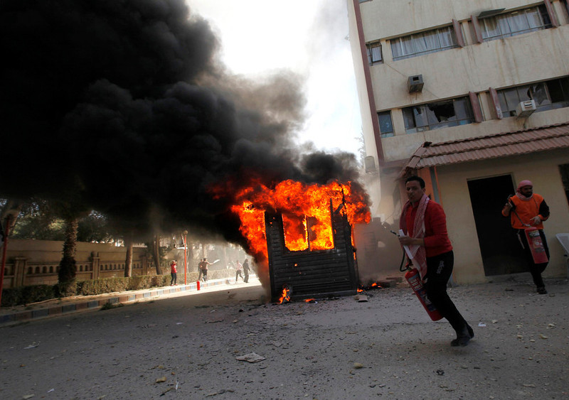 . A man runs with a fire extinguisher as smoke rises from buildings damaged by what activists said were shelling by forces loyal to President Bashar al-Assad in Raqqa province, eastern Syria, March 14, 2013.  REUTERS/Hamid Khatib