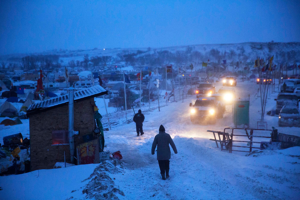 . A motorist checks the condition of an exit ramp before attempting to drive out of the Oceti Sakowin camp where people have gathered to protest the Dakota Access oil pipeline in Cannon Ball, N.D., Tuesday, Dec. 6, 2016. An overnight storm brought several inches of snow, winds gusting to 50 mph and temperatures that felt as cold as 10 degrees below zero. (AP Photo/David Goldman)