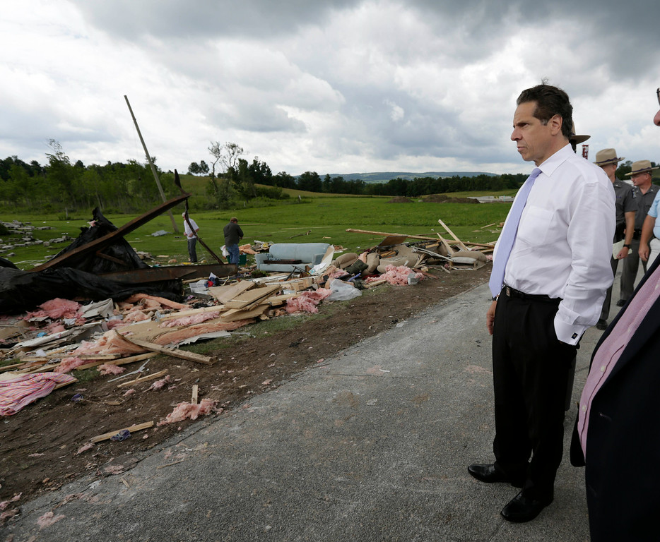 . New York Gov. Andrew Cuomo surveys the damage from Tuesday night\'s storm, on Wednesday, July 9, 2014, in Smithfield, N.Y. The National Weather Service has confirmed that a tornado destroyed the homes in upstate New York where four people were killed. (AP Photo/Mike Groll)