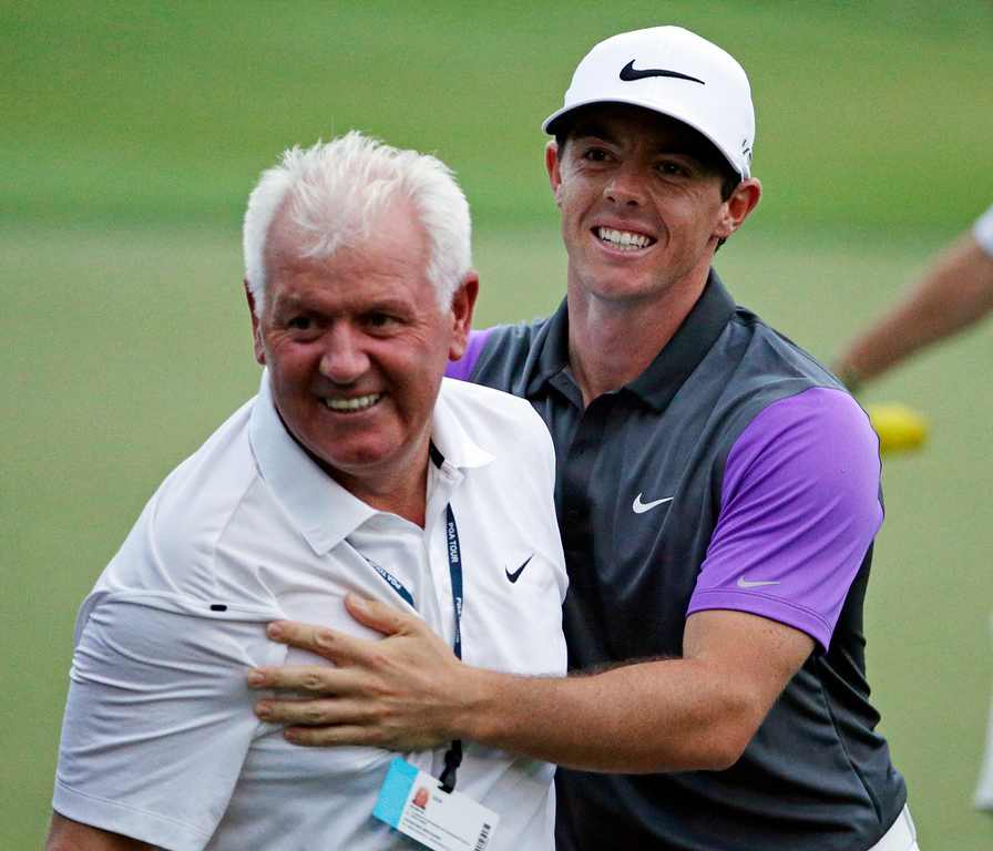. Rory McIlroy, of Northern Ireland, celebrates with is father, Gerry, after winning  the PGA Championship golf tournament at Valhalla Golf Club on Sunday, Aug. 10, 2014, in Louisville, Ky. (AP Photo/John Locher)