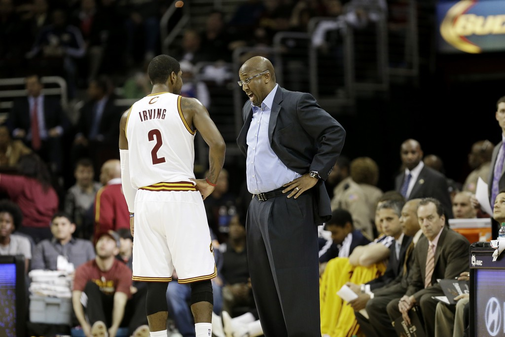 . Cleveland Cavaliers head coach Mike Brown talks to Kyrie Irving (2) in an NBA basketball game against the Detroit Pistons Monday, Dec. 23, 2013, in Cleveland. (AP Photo/Mark Duncan)