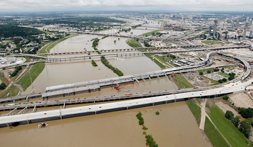 . Motorist commute across Interstate 35E, bottom, over a swollen Trinity River just south of downtown Dallas, Friday, May 29, 2015. Floodwaters submerged Texas highways and threatened more homes Friday after another round of heavy rain added to the damage inflicted by storms. (AP Photo/Brandon Wade)
