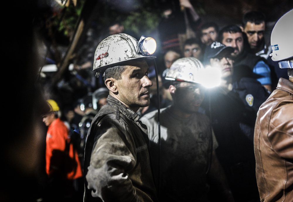 ". Miners wait at the gate of a mine after an explosion in Manisa on May 13, 2014. Four miner were killed and as many as 300 trapped after a mine collapse in the western Turkish city of Manisa, a local official said. ""At least 200-300 workers were working in the mine when an electric fault caused an explosion,\"" the mayor of Soma, a district of Manisa, told private NTV television. (BULENT KILIC/AFP/Getty Images)"