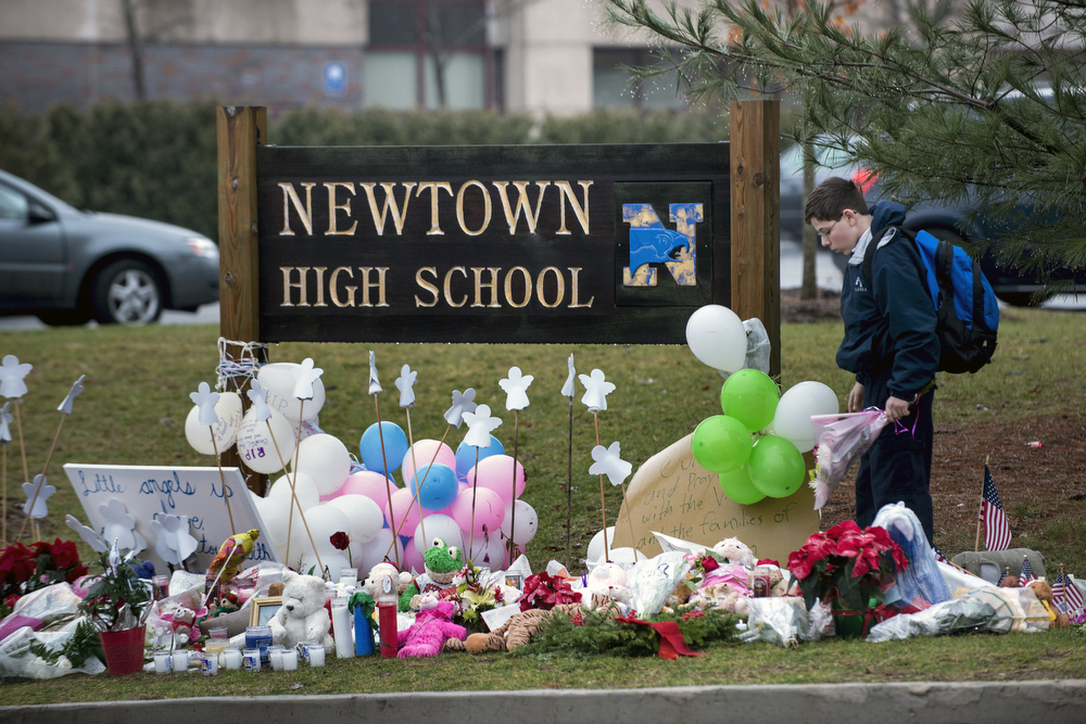 Description of . A student looks for a place to leave flowers at a makeshift memorial for the victims of the Sandy Hook Elementary School shooting at the entrance of Newtown High School December 18, 2012 in Newtown, Connecticut. Students in Newtown, excluding Sandy Hook Elementary School, return to school for the first time since last Friday's shooting at Sandy Hook which took the live of 20 students and 6 adults.  BRENDAN SMIALOWSKI/AFP/Getty Images
