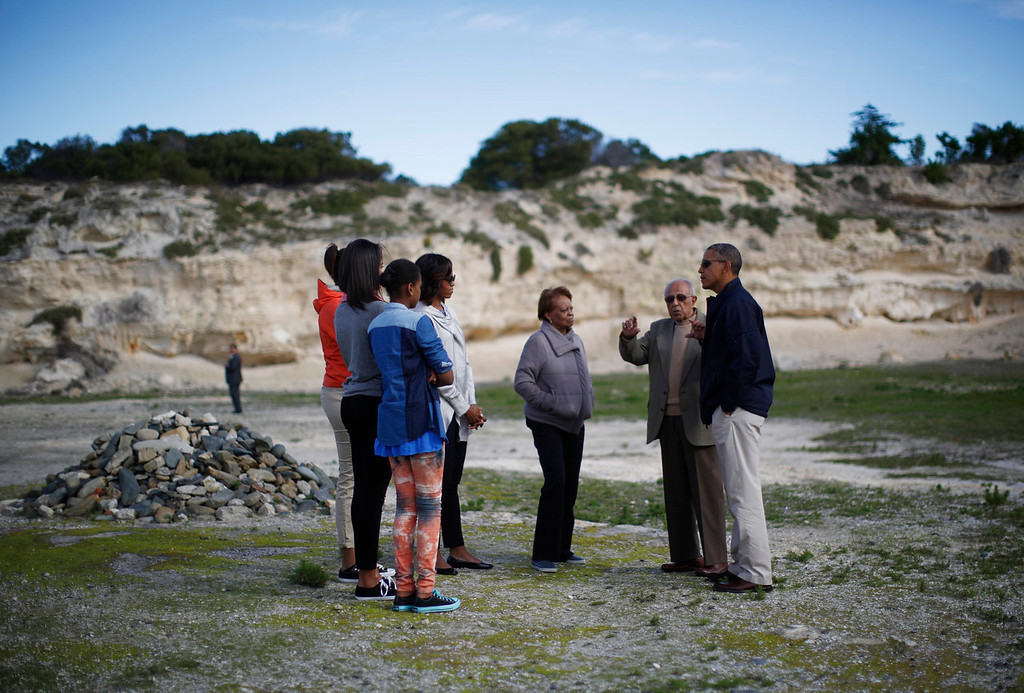 . U.S. President Barack Obama is pictured with his family, as he visits the rock quarry labor camp where Nelson Mandela was forced to work as a prisoner on Robben Island near Cape Town, South Africa on June 30, 2013. The Obamas visited the bleak former prison island off the coast of South Africa on Sunday to pay tribute to ailing anti-apartheid hero Mandela. Pictured with the first family is their guide Ahmed Kathrada (2nd R).  REUTERS/Jason Reed