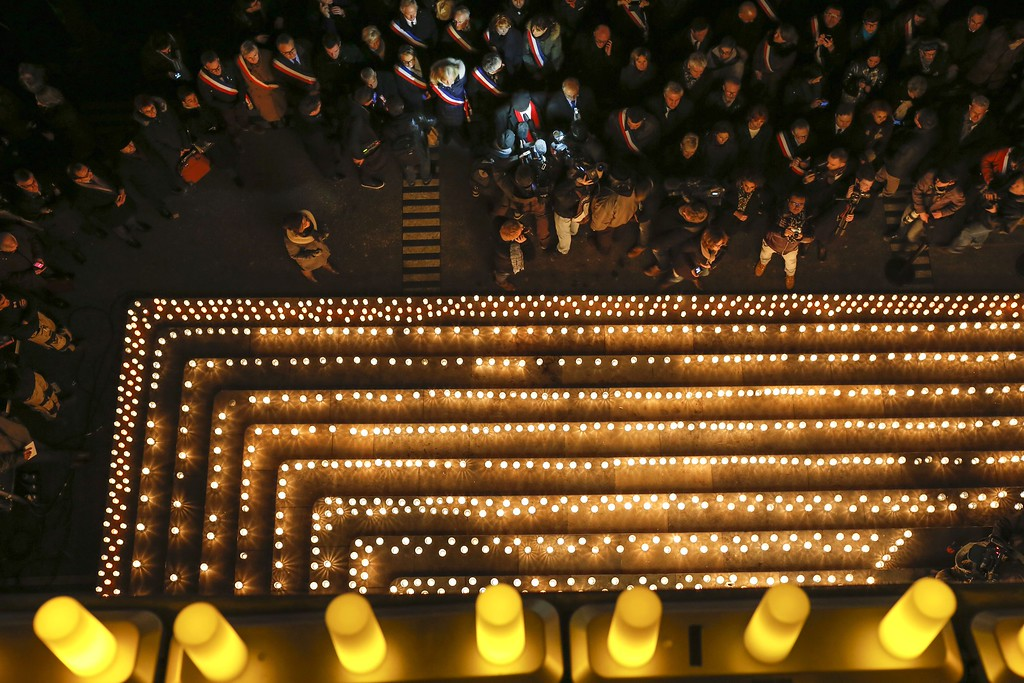 . People gather near candles lit to commemorate the victims of a deadly attack at the Paris offices of French satirical newspaper Charlie Hebdo, in Lyon, central France, Wednesday, Jan. 7, 2015. Masked gunmen stormed the Paris offices of a weekly newspaper that caricatured the Prophet Muhammad, killing at least 12 people, including the editor, before escaping in a car. It was France\'s deadliest postwar terrorist attack. (AP Photo/Laurent Cipriani)