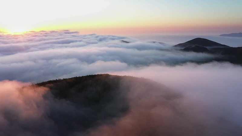 Available in 4K -Aerial video clip with magical sunset over a low cloud layer covering Pico Island, The Azores