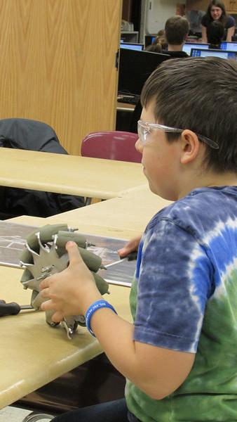 Colin works on tightening an mecanum wheel.
