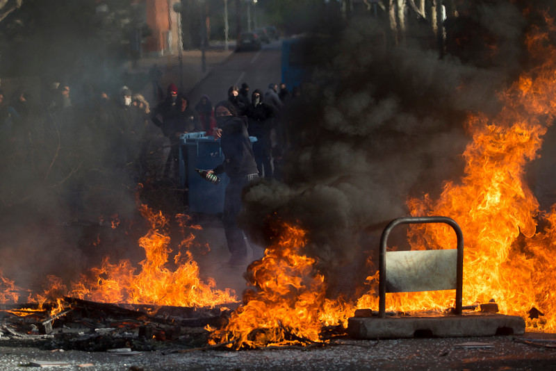 . A student throws a bottle through the barricade made as others block the street during the first day of  a student strike to protest a government education reform and cutbacks in grants and staffing, at Complutense Universtity in Madrid, Spain, Wednesday, March 26, 2014. Spanish police say they have arrested more than 50 students when the police moved in to end the occupation of a campus building after the university had asked them to intervene. Students, many with their faces covered, set fire to trash containers and set up barricades on at least two streets in the university complex during the protest. (AP Photo/Andres Kudacki)