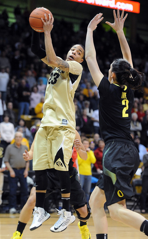 . Chucky Jeffery of CU gets a rebound in front of Danielle Love of Oregon. Cliff Grassmick / February 10, 2013