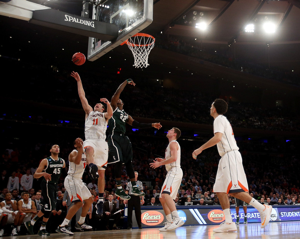 . Evan Nolte #11 of the Virginia Cavaliers goes to the hoop against Branden Dawson #22 of the Michigan State Spartans during the regional semifinal of the 2014 NCAA Men\'s Basketball Tournament at Madison Square Garden on March 28, 2014 in New York City.  (Photo by Bruce Bennett/Getty Images)