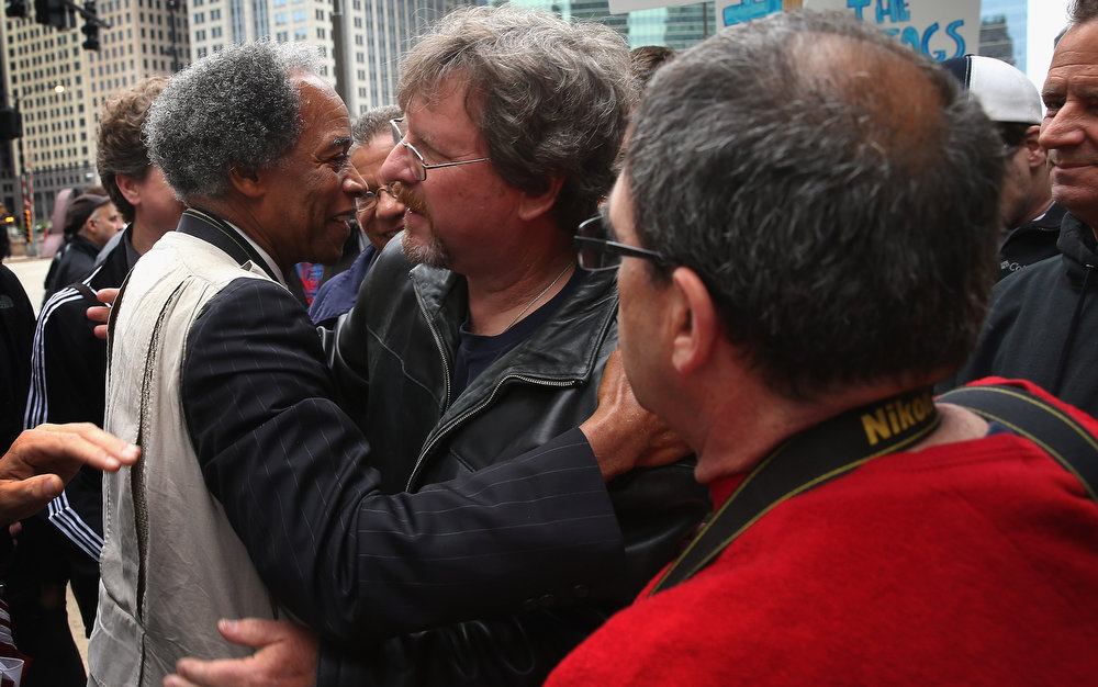 . Former Chicago Sun-Times photographers Pulitzer Prize winner John White (L) Tom Cruz (C), and Scott Stewart greet each other during a demonstration outside the offices of the Sun-Times on June 6, 2013 in Chicago, Illinois. Union members, reporters, and photographers gathered outside the newspaper\'s office to protest the company\'s decision last week to eliminate its 28-member photo staff. The newspaper chain plans to train their reporters to take pictures with iPhones to fill the void.  (Photo by Scott Olson/Getty Images)