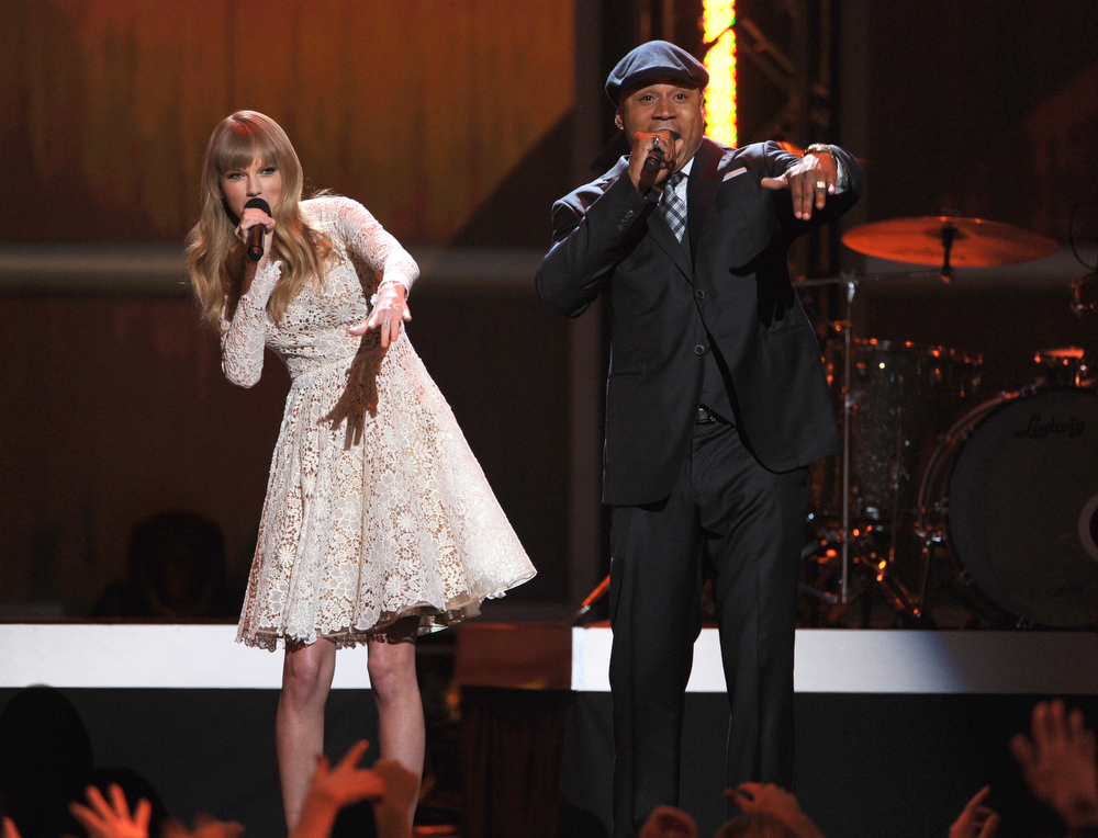 Description of . Co-hosts Taylor Swift and LL Cool J speak onstage at The GRAMMY Nominations Concert Live!! held at Bridgestone Arena on December 5, 2012 in Nashville, Tennessee.  (Photo by Kevin Winter/Getty Images)