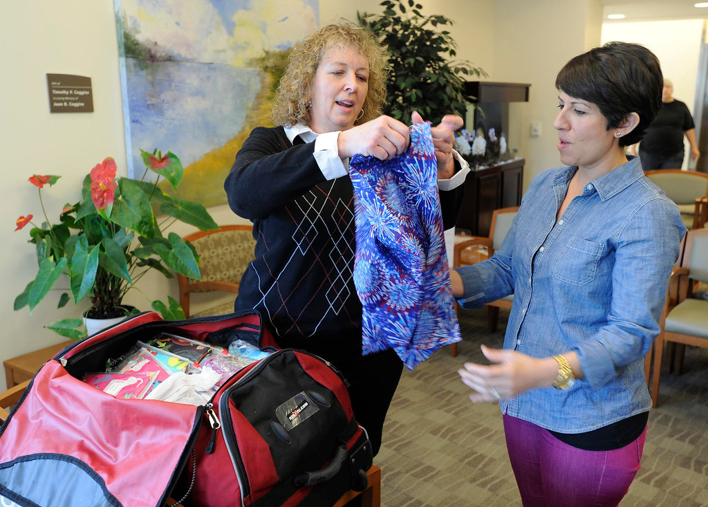 . Brenda Jones shows an IV Pole cover to Liz Barnett. Jones created her own open-in-the-front wrap when she was undergoing treatment for breast cancer, crafting an option to the hospital gown, utilizing soft and colorful flannel fabrics. Fellow patients loved them and her nonprofit Hug Wraps was born. Jones visited Providence Saint Joseph Medical Center�s Roy and Patricia Disney Family Cancer Center and gave patients free wraps. Burbank, CA 2/22/2013(John McCoy/Staff Photographer)