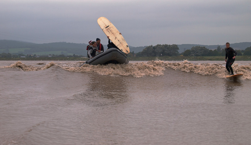 Steve King riding the bore whilst Sergio Laus on the boat is about to join him with his longboard.
