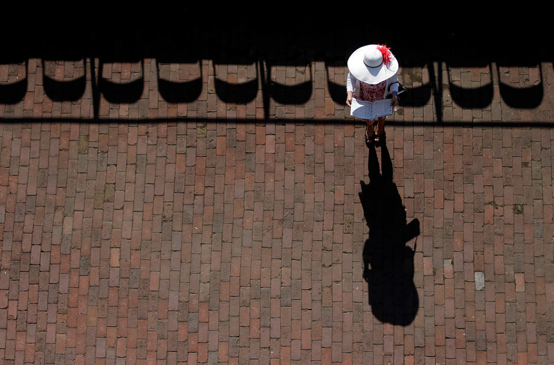 . A woman checks her racing program before the 140th running of the Kentucky Derby horse race at Churchill Downs Saturday, May 3, 2014, in Louisville, Ky. (AP Photo/Charlie Riedel)