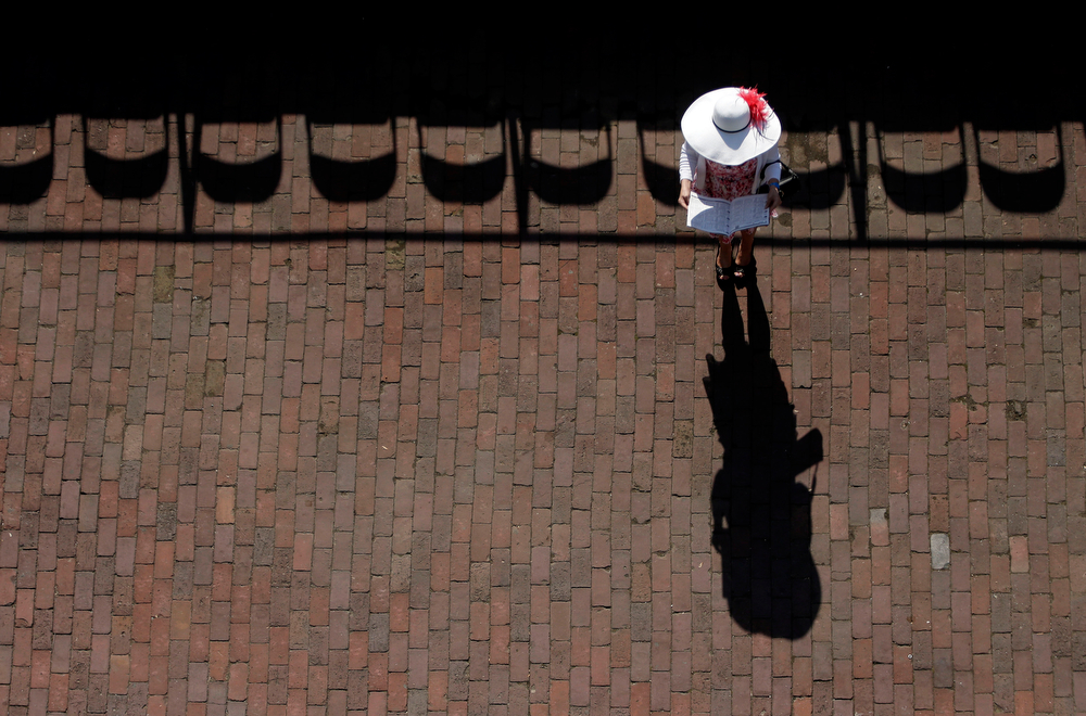 Description of . A woman checks her racing program before the 140th running of the Kentucky Derby horse race at Churchill Downs Saturday, May 3, 2014, in Louisville, Ky. (AP Photo/Charlie Riedel)