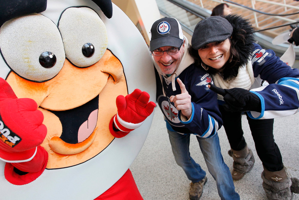 Description of . Hockey fans Allen Hurton, center, and Bessie Hatzitrifonos celebrate with a Peter Puck mascot outside the arena before the season-opening NHL hockey game between the Ottawa Senators and Winnipeg Jets in Winnipeg, Manitoba, on Saturday, Jan. 19, 2013.(AP Photo/The Canadian Press, John Woods)