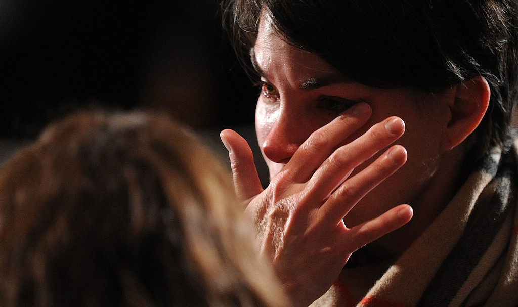 . NEWTOWN, CT - DECEMBER 16:  A mourner cries before U.S. President Barack Obama speaks at an interfaith vigil for the shooting victims from Sandy Hook Elementary School on December 16, 2012 at Newtown High School in Newtown, Connecticut. Twenty-six people were shot dead, including twenty children, after a gunman identified as Adam Lanza opened fire at Sandy Hook Elementary School. Lanza also reportedly had committed suicide at the scene. A 28th person, believed to be Nancy Lanza, found dead in a house in town, was also believed to have been shot by Adam Lanza. (Photo by Olivier Douliery-Pool/Getty Images)
