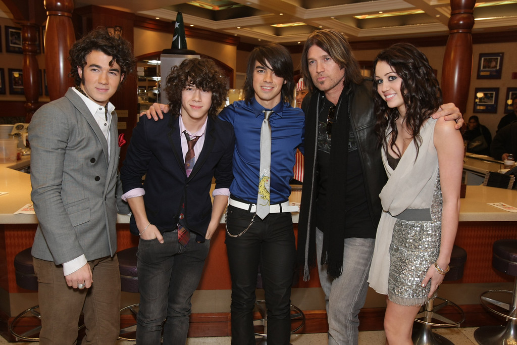 """. HOLLYWOOD, CALIFORNIA - JANUARY 17: Kevin Jonas, Nick Jonas, Joe Jonas, Billy Ray Cyrus and Miley Cyrus at the World Premiere of Walt Disney Pictures\' \""""Hannah Montana & Miley Cyrus: Best of Both World Concert\"""" on January 17, 2008 at the El Capitan Theatre in Hollywood, CA. (Photo by Eric Charbonneau/Invision/AP Images)"""