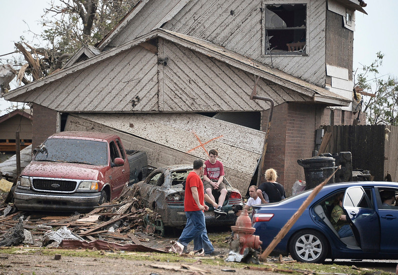 . People are seen next to a damaged house and vehicles along a street after a huge tornado, in Moore, Oklahoma May 20, 2013. A 2-mile-wide (3-km-wide) tornado tore through the Oklahoma City suburb of Moore on Monday, killing at least 51 people while destroying entire tracts of homes, piling cars atop one another, and trapping two dozen school children beneath rubble.  REUTERS/Gene Blevins