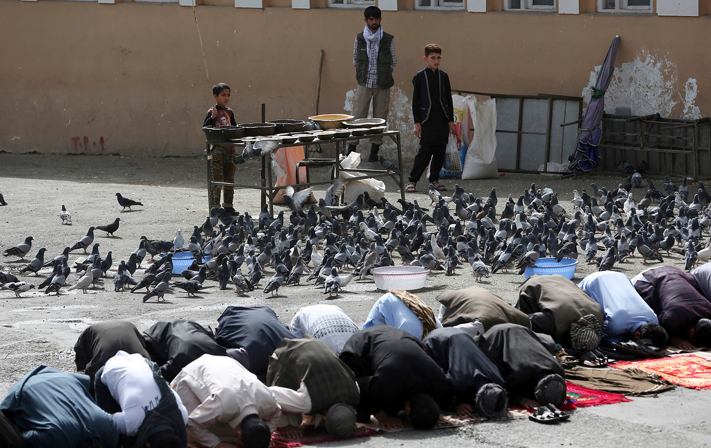 . People attend Eid al-Fitr prayers outside of Shah-e-Dushamshera mosque in Kabul, Afghanistan, Friday, June 15, 2018. Taliban, an insurgent group who fight against NATO and Afghanistan\'s government, announced that they will start a 3-day ceasefire, starting in the first day of Eid al-Fitr. (AP Photo/Massoud Hossaini)
