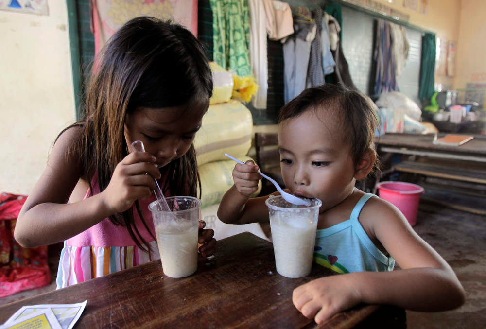 Description of . Children eat porridge at an evacuation centre for residents who were rendered homeless after their houses were swept by floodwaters at the height of Typhoon Bopha, in New Bataan town in Compostela Valley, southern Philippines December 8, 2012. Philippine President Benigno Aquino declared a state of national calamity on Saturday, four days after this year\'s strongest typhoon left nearly 1,000 people dead or missing mostly in the country\'s resource-rich south. REUTERS/Erik De Castro