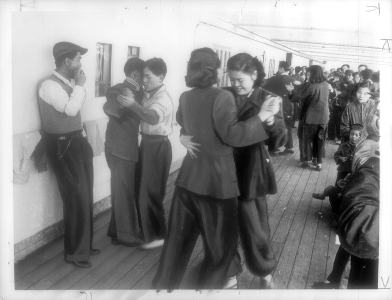 """""""Teen-agers dance on deck of Kean Maru which brought exiles from China, while older people peer ahead for first sight of land they longed for during Red opressions.""""--caption on photograph"""