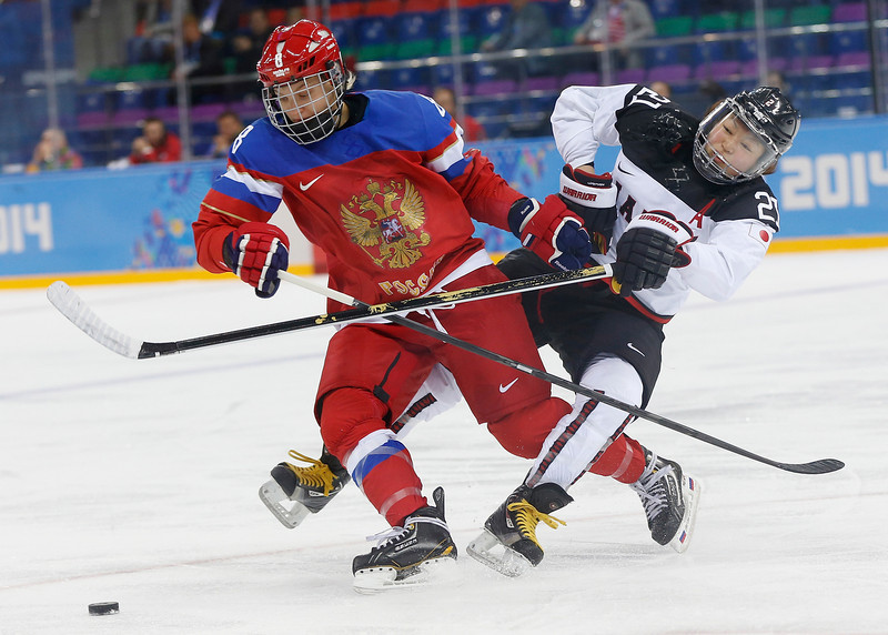 . Iya Govrilova of Russia and Hanae Kubo of Japan get tangled up fighting for control of the puck during the first period of the 2014 Winter Olympics women\'s ice hockey game at Shayba Arena, Tuesday, Feb. 11, 2014, in Sochi, Russia. (AP Photo/Petr David Josek)