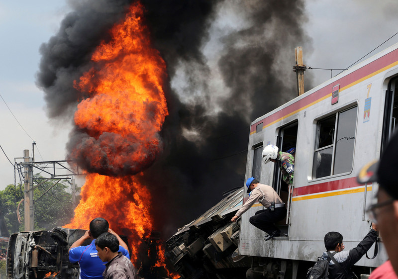 . Dark thick smoke billows from the fire after a commuter train collided with a truck hauling fuel on the outskirts Jakarta, Indonesia, Monday, Dec. 9, 2013. (AP Photo/Tatan Syuflana)