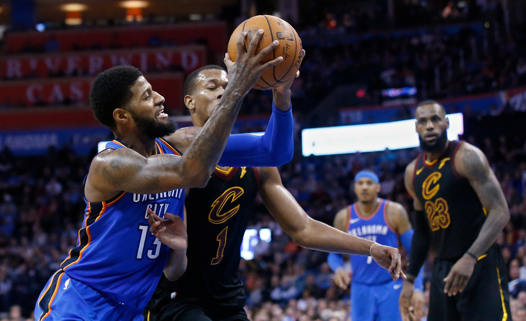 . Oklahoma City Thunder forward Paul George (13) drives past Cleveland Cavaliers guard Rodney Hood (1) during the second half of an NBA basketball game in Oklahoma City, Tuesday, Feb. 13, 2018. (AP Photo/Sue Ogrocki)