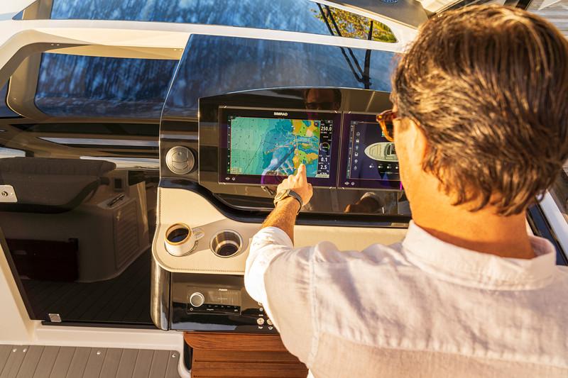2021-Sundancer-370-Outboard-DAO370-lifestyle-hand-man-helm-dash-Simrad-06723.jpg