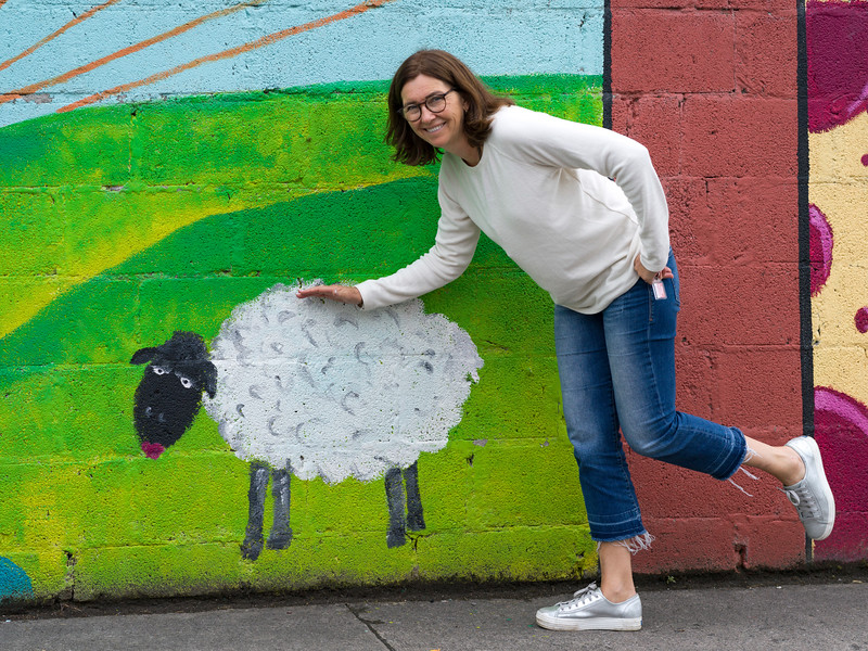 Portrait of a woman gesturing against sheep painting, Kiltimagh, County Mayo, Ireland