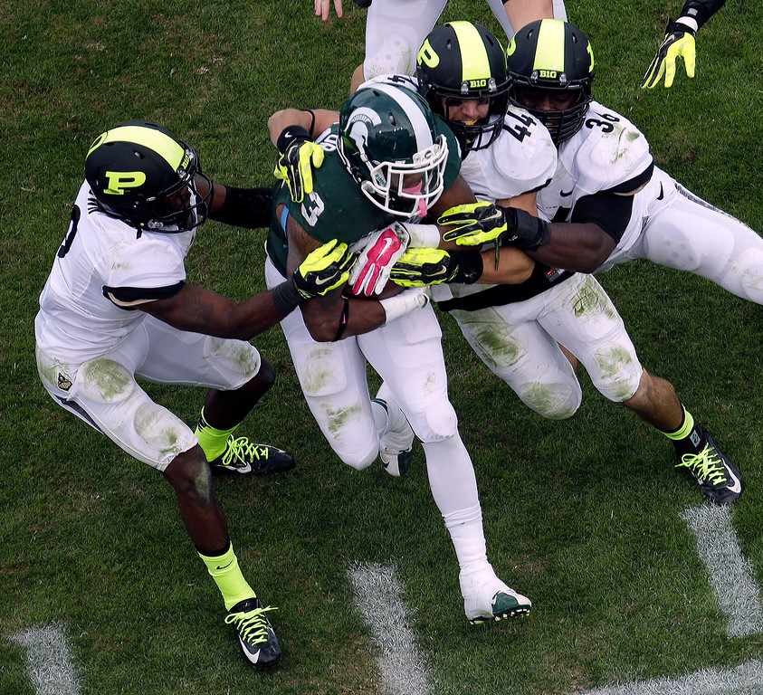 . Michigan State running back Jeremy Langford (33) gets tackled by a gang of Purdue defenders during the second half of an NCAA college football game in West Lafayette, Ind., Saturday, Oct. 11, 2014. Michigan State won 45-31. (AP Photo/AJ Mast)