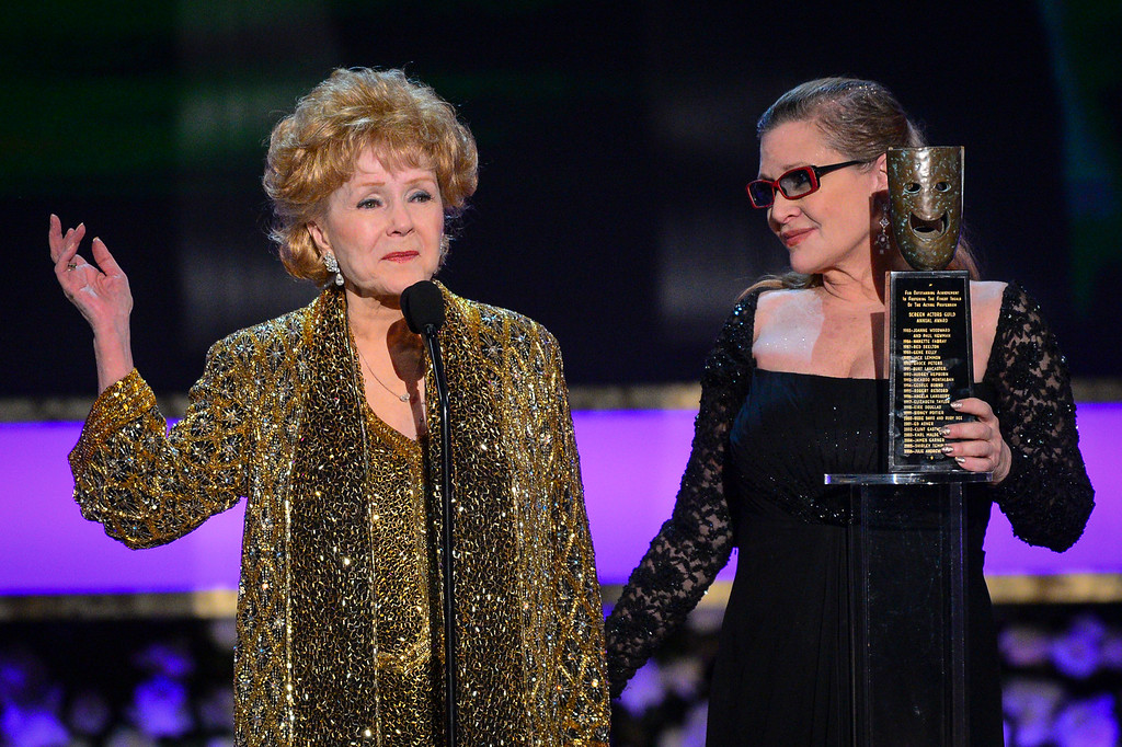 ". Carrie Fisher presents her mother, Debbie Reynolds, with the lifetime achievement award at the 21st Annual Screen Actors Guild Awards telecast at the Shrine Auditorium in Los Angeles, California on Sunday January 25, 2014.  Reynolds, star of the 1952 classic ""Singin\' in the Rain\"" died Wednesday, Dec. 28, 2016. She was 84. Her daughter, Fisher, died Dec. 27, 2016. (Photos by Michael Owen Baker, Los Angeles Daily News/SCNG)"