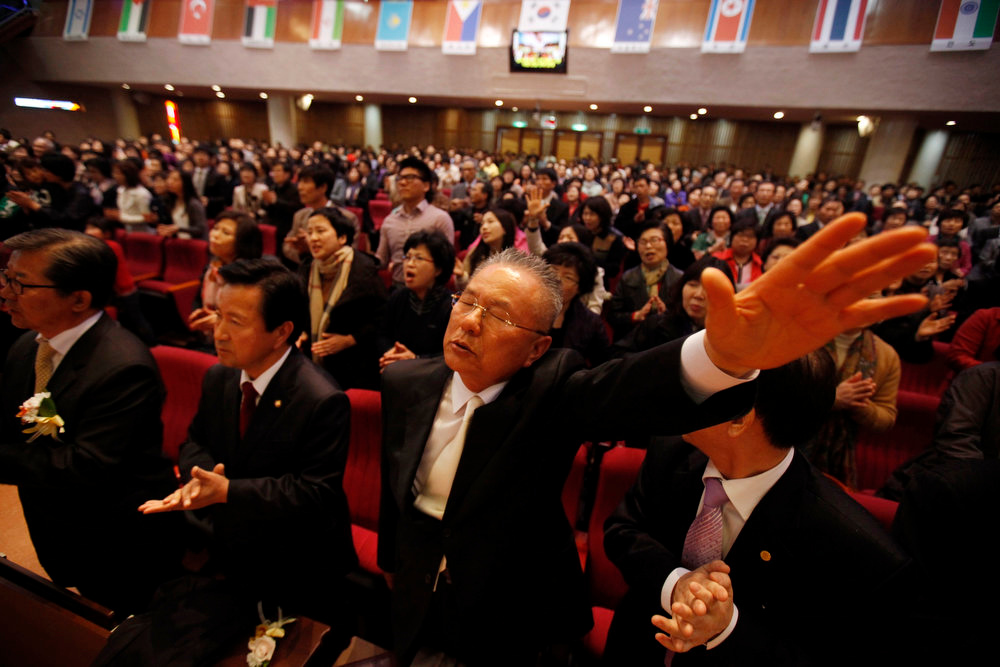. South Korean Christians pray for peace on Korean peninsula and North Korea as North Korean national flag (3rd R) is seen among other countries\' national flags during an annual Easter mass service at a church in Icheon, about 80 km (50 miles) southeast of Seoul March 31, 2013. Holy Week is celebrated in many Christian traditions during the week before Easter.  REUTERS/Kim Hong-Ji