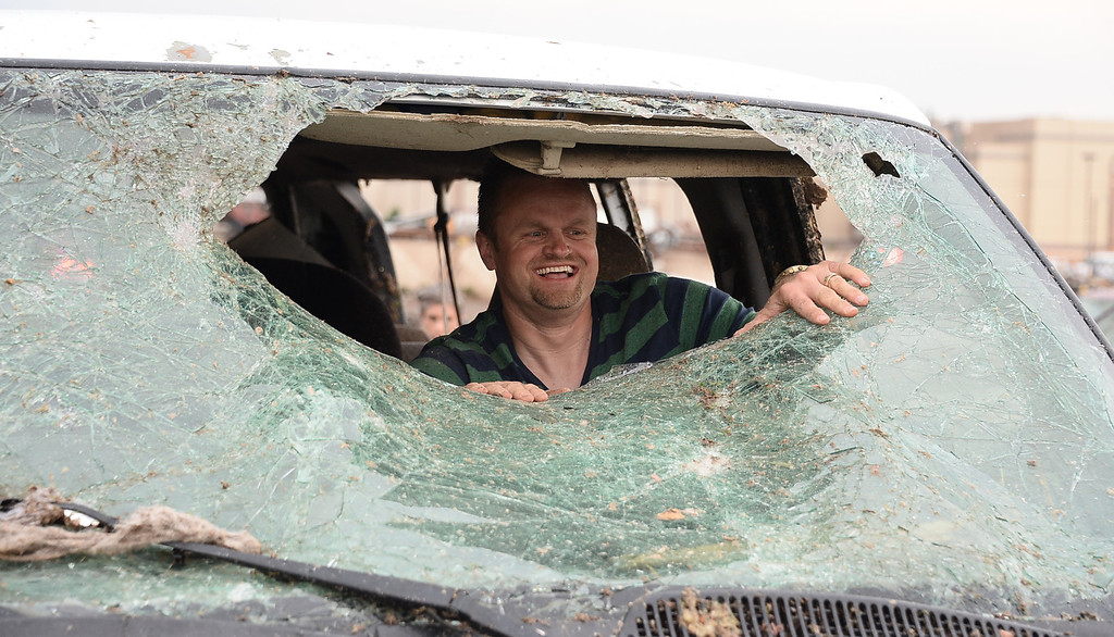 . Larry Hutcheson knocks out the windshield of his van so he can drive it home at the Moore hospital parking lot. 