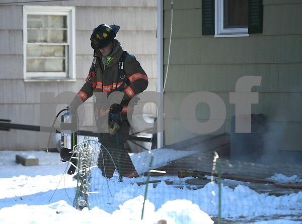 12/39/2017 Mike Orazzi | Staff Bristol firefighters extinguish a fire behind a home on Rich Lane caused by fireplace ashes placed behind a home Friday afternoon.