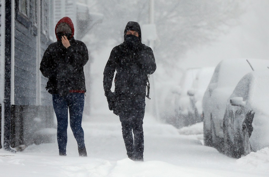 . A couple walks on Marginal Street in Boston, Tuesday, March 13, 2018. Boston finds itself in the bullseye of the third nor\'easter in two weeks, with forecasters warning of up to 18 inches of snow and 2 feet or more to the south. (AP Photo/Michael Dwyer)