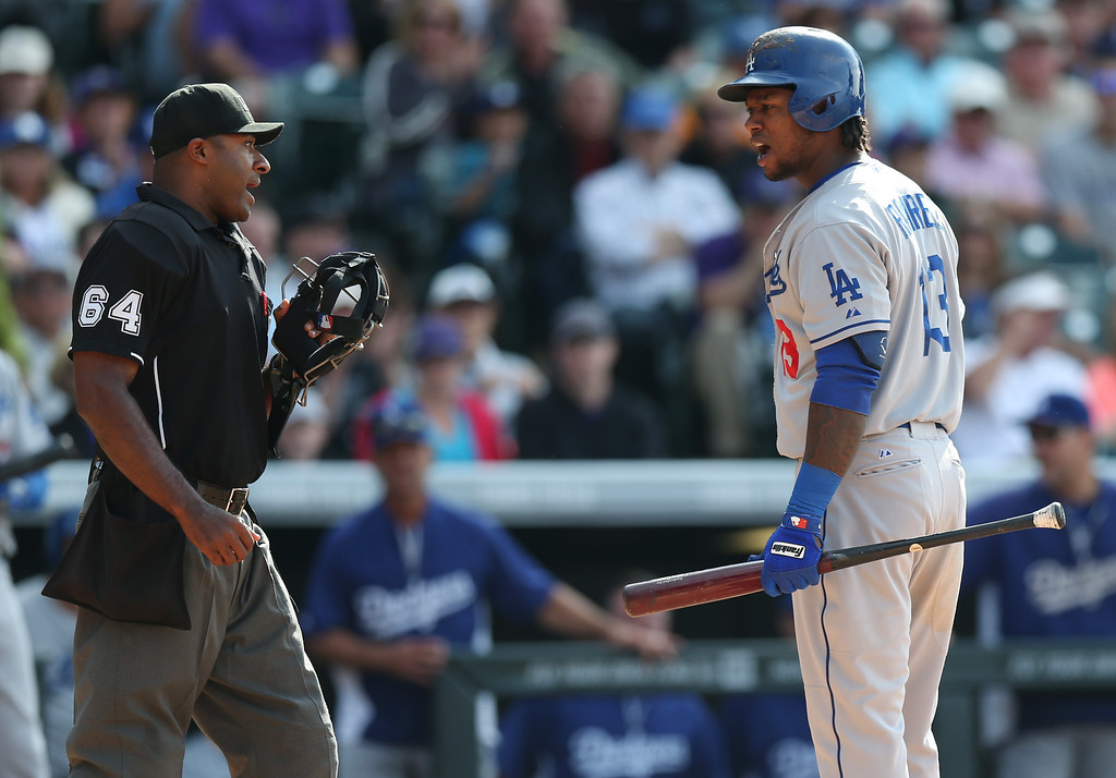 . Los Angeles Dodgers\' Hanley Ramirez, right, argues after he was called out on strikes by home plate umpire Alan Porter while facing the Colorado Rockies in the ninth inning of the Rockies\' 5-4 victory in 10 innings in a baseball game in Denver on Saturday, June 7, 2014. (AP Photo/David Zalubowski)