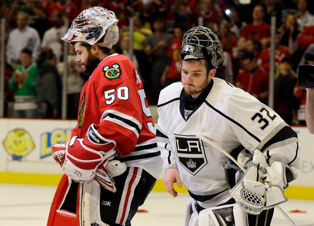 . Los Angeles Kings goalie Jonathan Quick (32) laves after congratulating Chicago Blackhawks goalie Corey Crawford (50) for Blackhawks\' 4-3 win over Los Angeles Kings in the second overtime period in Game 5 of the NHL hockey Stanley Cup playoffs Western Conference finals, Saturday, June 8, 2013, in Chicago. The Blackhawks advance to the Stanley Cup finals. (AP Photo/Nam Y. Huh)